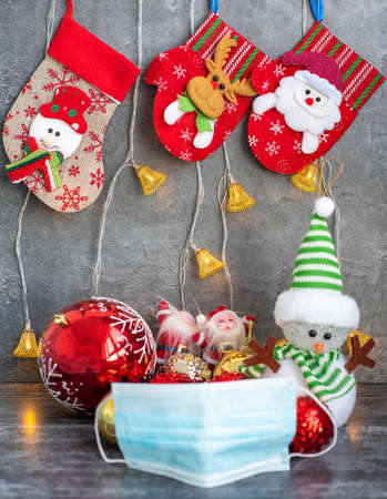 Background with a medical mask with a Christmas red stocking on the fireplace and toys Stock Photo