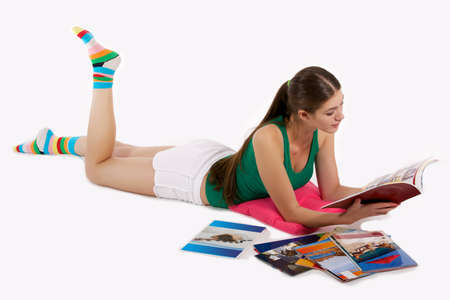 girl is lying on the floor and read magazine
