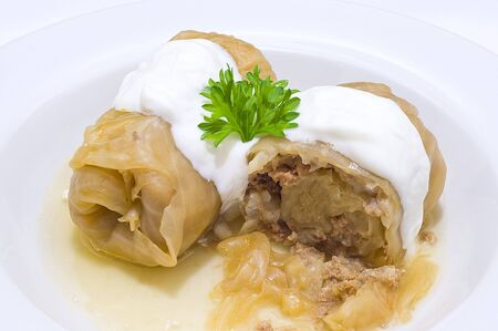 Cabbage stuffed with meat, ornated with cream and parsley Stock Photo
