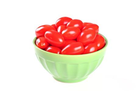 Tasty cherry tomatos in a bowl, white background