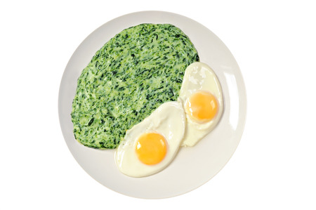 Spinach with fried eggs on a plate, white background