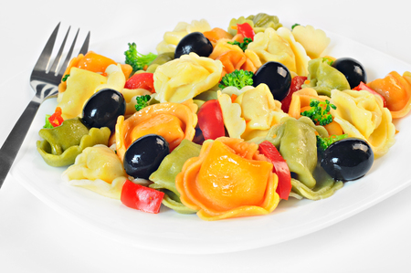 Salad made with tortellini, olives, broccoli, red pepper, on a plate, white background Stock Photo
