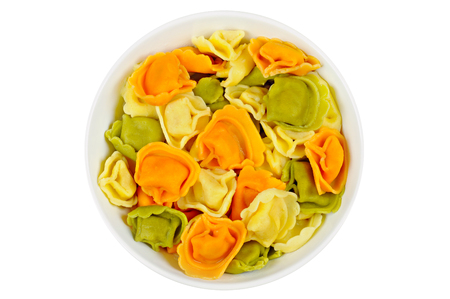 Raw colored tortellini in a bowl, on a white background