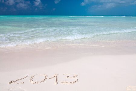 Year 2013 hand written on the white sand in front of the sea Stock Photo - 13325723