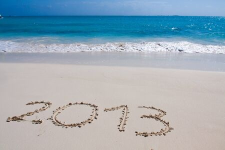 Year 2013 hand written on the white sand in front of the sea photo