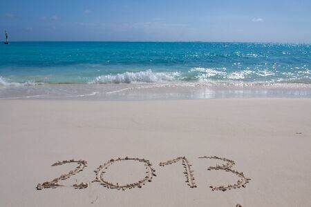 Year 2013 hand written on the white sand in front of the sea Stock Photo - 13325754