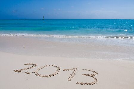 Year 2013 hand written on the white sand in front of the sea Stock Photo - 13325728
