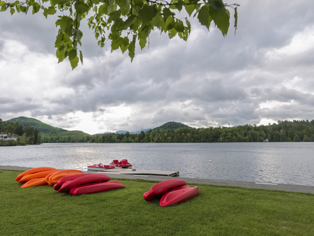 View of colorful boats stacked on the shore of Mirror Lake with the Adirondack mountains in the background. Stock Photo
