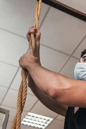 boy pulling the rope in the gym. working out