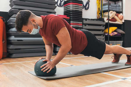 boy exercising with ball in the gym