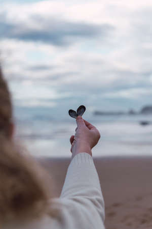 Woman holding a heart shaped shell in front of the sea