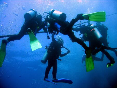 Divers doing a decompression safety stop Stock Photo