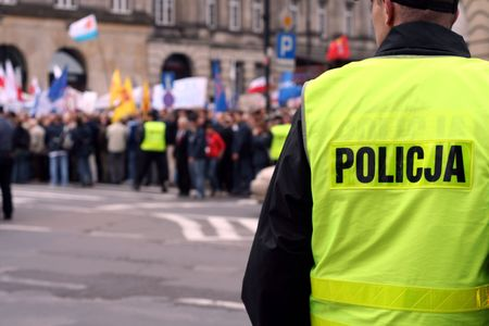 purposely: Police officer talking on a radio protecting an anti-government demonstration in Warsaw Poland on 7 October 2006 (Blue March by Platforma Obywatelska). Purposely taken with a shallow DOF not to detail faces.
