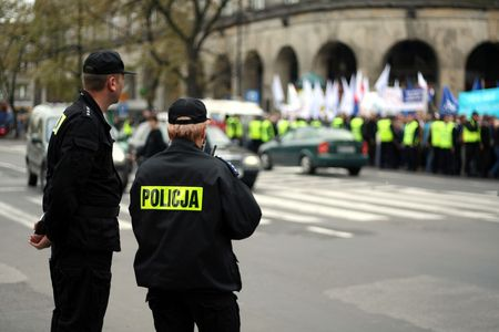 purposely: Police officers talking on a radio protecting an anti-government demonstration in Warsaw Poland on 7 October 2006 (Blue March by Platforma Obywatelska). Purposely taken with a shallow DOF not to detail faces. Stock Photo