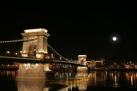 Szechenyi Chain Bridge connecting Buda and Pest sides of the Hungarian capital Budapest at full moon photo