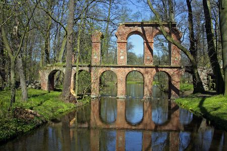 Antique roman aqueduct reflecting in a pool of water