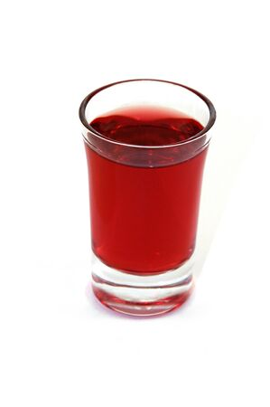 Isolated shot glass filled with red alcoholic beverage