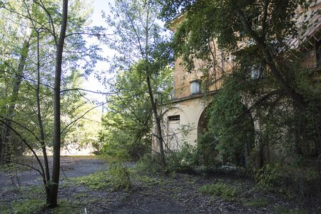 An abandoned seminary surrounded by vegetation