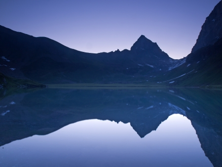 Mountain range mirroring at daybreak  Seewlisee Switzerland  photo