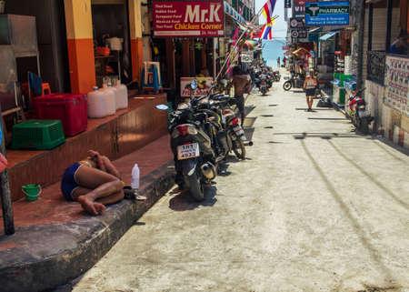 Koh Phangan, Thailand- April 20 2019: Haad rin beach street after Full Moon party, sleeping tourist