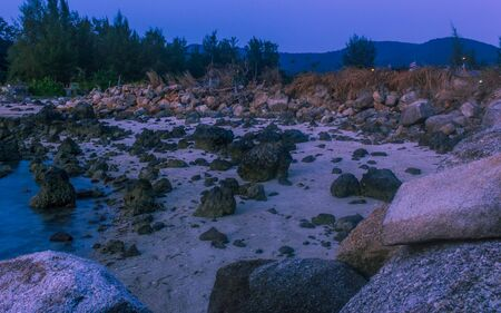 Thailand island full moon at sunset time, rocks foreground
