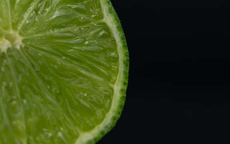 Green lime citruss fruit cutting half macro fiber inside, black background