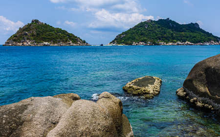 Two small green island view from Koh Tao bay, crystal blue water., large rocks fore ground.