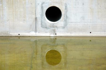 runoff: Storm Drain with reflection in water below Stock Photo