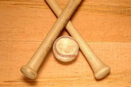 hardball: Two Baseball bats crossed with worn baseball between hamdles