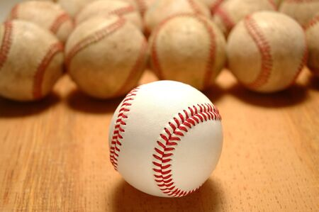 hardball: New baseballs in front of group of old worn baseballs - selective DOF