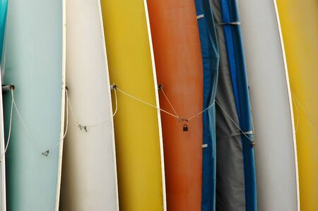 ketch: Row of Canoes Standing on End Stock Photo