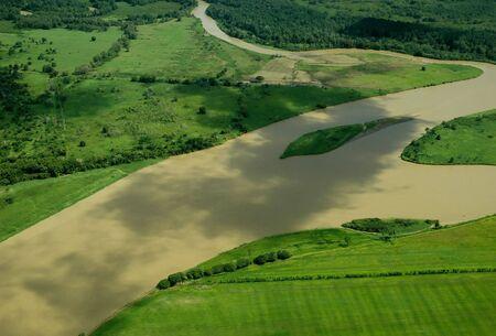 Aerial shot of Muddy River flowing through farmland