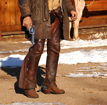 spurs: Cowboy in chaps & spurs holding revolver by side Stock Photo