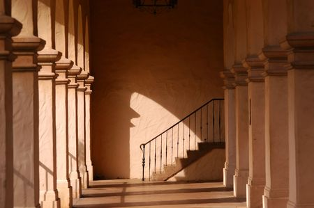 archway: Columns and archway stairs iron railing chandelier Stock Photo