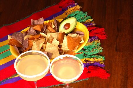 Avocado in platter of corn chips on Mexican table cloth with Margaritas photo