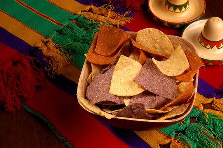 Corn chips in bowl on table with Mexican theme photo