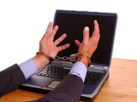 handcuffed hands: Businessmans handcuffed hands reaching towards laptop computer screen - isolated over white Stock Photo