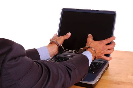 Businessmans handcuffed hands grabbing at laptop computer screen - isolated over white photo