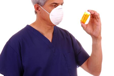Doctor in scrubs and mask holding pill bottle isolated over white Stock Photo - 953476