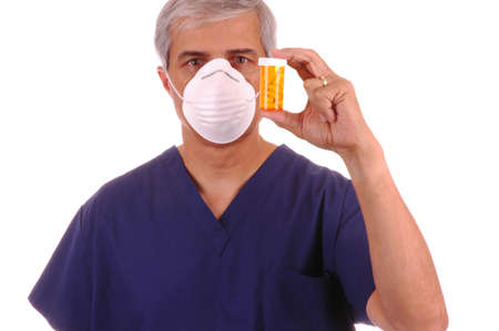 Doctor in scrubs and mask holding pill bottle isolated over white Stock Photo - 953477