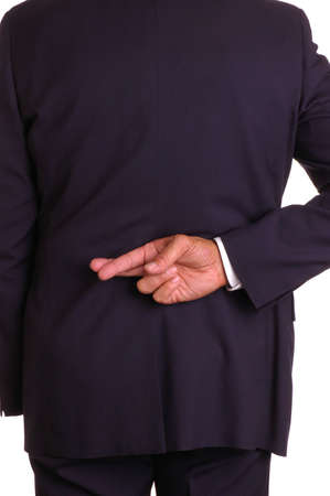 untruth: Businessman in dark suit with crossed fingers behind his back
