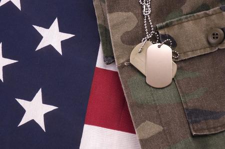 Las etiquetas de perro militares en bandera americana y fatigan