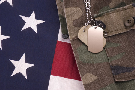 Military Dog Tags on American Flag and fatigues