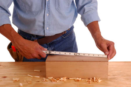 toolbelt: Carpenter wearing a toolbelt measuring wooden box, isolated over white