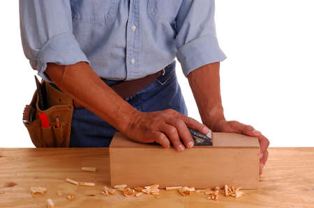 Carpenter wearing a toolbelt sanding a wooden box, isolated over white