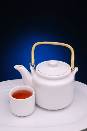 White Tea Pot and Cup on plate with blue spotlight background