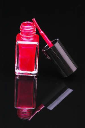 nail polish bottle: Red Nail Polish with Brush Leaning on Bottle on Black Glass Reflective background