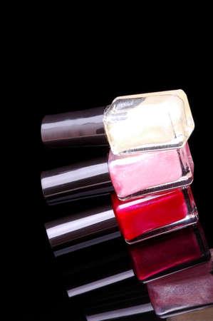 nail polish bottle: Three Colors of Nail Polish Bottles Stacked  Black Glass Reflective Background Stock Photo