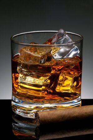 unhealthful: Cigar resting in front of a  Glass of Whiskey and Ice cubes on black reflective surface Stock Photo