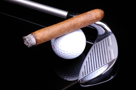 ashes: Cigar on Golf Ball and Cigar on black background with reflections